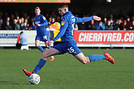 AFC Wimbledon defender Steve Seddon (15) with a shot on goal during the EFL Sky Bet League 1 match between AFC Wimbledon and Doncaster Rovers at the Cherry Red Records Stadium, Kingston, England on 9 March 2019.