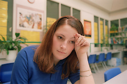 Portrait of teenage girl sitting in school classroom looking sad,