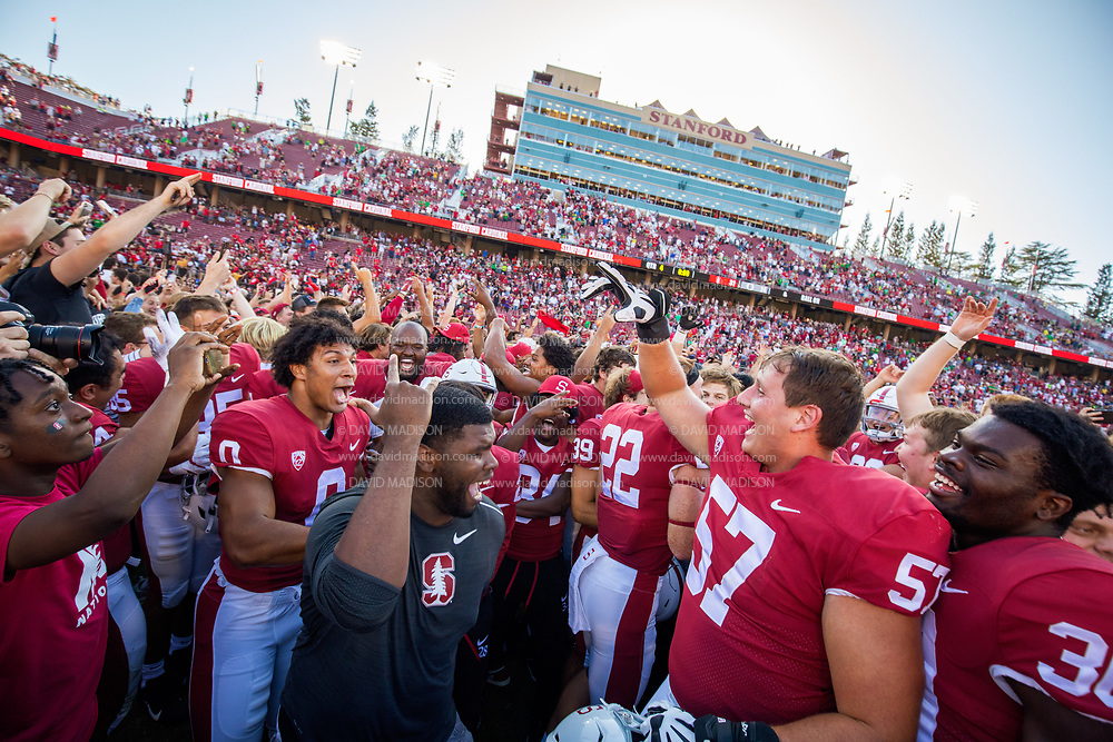 PALO ALTO, CA - OCTOBER 2:  Stanford Cardinal football players and fans celebrate on the field after the Stanford's 31-24 overtime victory over the Oregon Ducks in a Pac-12 college football game on October 2, 2021 at Stanford Stadium in Palo Alto, California; wearing black shirt is former Cardinal defensive lineman Wesley Annan, at left is Aeneas DiCosmo #0, at right is Levi Rogers #57 and Ese Dubre #30. (Photo by David Madison/Getty Images)