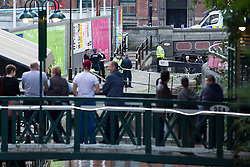 "© Licensed to London News Pictures . 06/10/2013 . Manchester , UK . Onlookers watch as police wait as the lock is drained . Police pull a body from The Bridgewater Canal in Manchester , adjacent to the City's "" Gay Village "" . The body was spotted yesterday (6th October) afternoon and a cordon was erected as specialist police divers made the recovery . Photo credit : Joel Goodman/LNP"