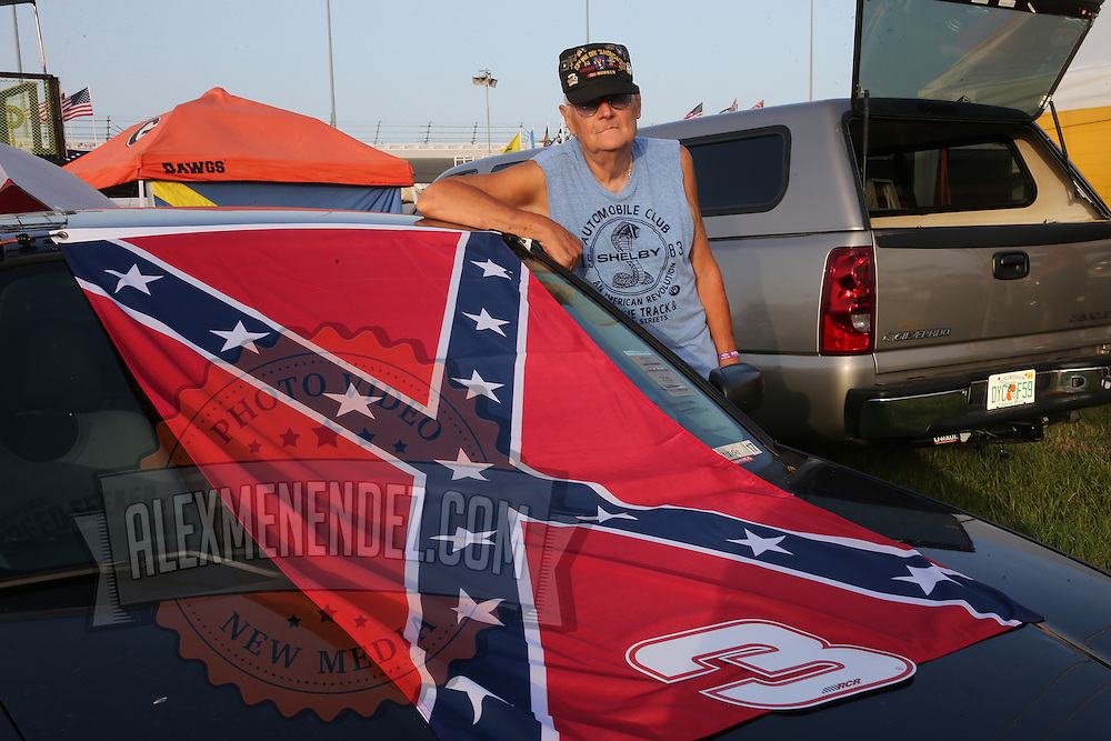 Larry, a U.S. war veteran, shows off his Confederate flag at his camp in the infield during the 57th Annual NASCAR Coke Zero 400 practice session at Daytona International Speedway on Friday, July 3, 2015 in Daytona Beach, Florida.  (AP Photo/Alex Menendez)