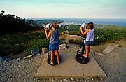 Two young girls look through binoculars at Penobscot Bay from the Camden Overlook in Camden, Maine, USA.
