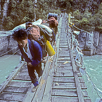 Porters cross a suspension bridge over the Po Tsangpo River in eastern Tibet.