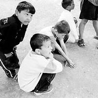 Young boys playing with marbles..Because of the war, fathers have disappeared or have been killed often being replaced as head of the family by their young son...During the summer1999, over 245,000 Serbs and Roms fled to Serbia and Montenegro from or within Kosovo in fear of reprisals from the majority Albanian population, after NATO air strikes had forced the withdrawal of Yugoslav. In 2003, less than 2% of them had returned and a large number of these internally displaced persons (IDPs) were still living in camps in very difficult conditions..In addition, around 5,000 IDPs, mainly of Roma ethnicity, are living in unrecognized collective centres, makeshift huts, corrugated metal containers and other substandard shelters. .This work was meant to look at how the life of children and young adults is affected by the fact that they are IDPs. I asked myself more specifically what would be different for these children/young adults from the 'normal' people of their age as far as education, health, social life, family, 'love' life and leisure are concerned. ..Jeunes garçons jouant aux billes..A cause de la guerre, des pères ont disparus ou ont été tués et sont remplacés par leur jeune fils à la tête de la famille...Pendant l'été 1999, plus de 245 000 serbes et roms ont fuit le Kosovo pour chercher refuge en Serbie ou au Montenegro, par peur de représailles de la part de la majorité de la population albanaise après que les forces de l'OTAN aient forcé l'armée yougoslave à se retirer. En 2003, moins de 2% d'entre eux étaient rentrés chez eux et le plus grand nombre de ces 'déplacés' (IDPs) vivaient encore dans des centres d'accueil dans des conditions très difficiles..Environ 5 000 IDPs, la plupart romas, vivent dans des centres non reconnus faits de containers ou d'abris de fortune. .Ce travail s'est focalisé sur les jeunes IDPs, sur les conséquences de leur état de 'déplacés' sur leur vie et plus particulièrement dans les sphères concernant l'éducation, la santé,  la vie so