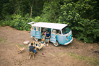 11 November 2020 - Rolante, Brazil: Aerial View Of Two People Camping In Lush Forest And Having a Picnic Beside a Blue Kombi Van In Rolante, Rio Grande do Sul, Brazil.