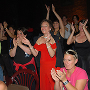 "Spectators and fellow same-sex dancers cheer as the announcement is made that Jazz Munteanu and Karin Stjarnefyr (umlaut on the ""a""), both of Sweden, (not shown in photo) have won the A category adult women's latin division championship of the same-sex ballroom dancing competition during the 2007 Eurogames at the Waagnatie hangar in Antwerp, Belgium on July 13, 2007. ..Over 3,000 LGBT athletes competed in 11 sports, including same-sex dance, during the 11th annual European gay sporting event. Same-sex ballroom is a growing sports that has been happening in Europe for over two decades."