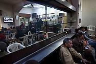 Men watch Al Jazeera in a cafe in Benghazi on March 4, 2011.