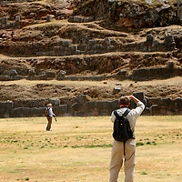 South America, Peru, Cusco. Visitor taking a picture at the fortress of Sacsayhuaman, on the outskirts of Cusco in the Andes.
