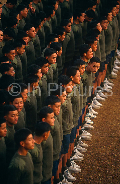 New recruits of the British Royal Gurkha Regiment learn to parade for their official photograph at their army camp in Pokhara, Nepal after recently being recruited into the regiment after a gruelling series of tests to eliminate the weaker and less able candidates, before the 160 lucky candidates travel to the UK for basic training. 60,000 boys aged between 17-22 (or 25 for those educated enough to become clerks or communications specialists) report to designated recruiting stations in the hills each November, most living from altitudes ranging from 4,000-12,000 feet. After initial selection, 7,000 are accepted for further tests from which 700 are sent down here to Pokhara in the shadow of the Himalayas. Only 160 of the best boys succeed in the journey to the UK. Nepal has been supplying youth for the British army since the Indian Mutiny of 1857.