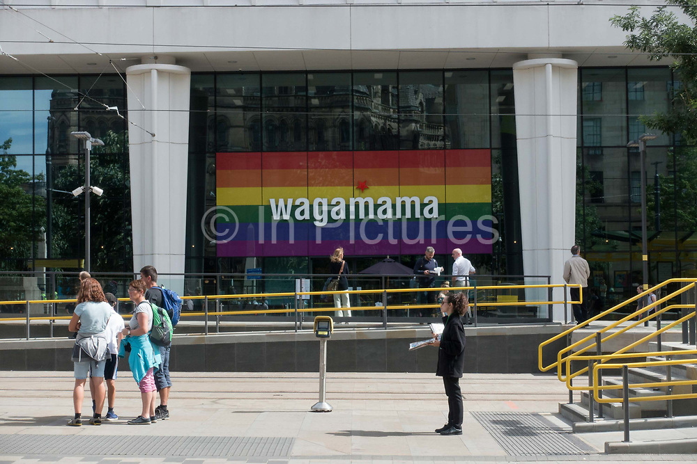 Colours of the rainbow displayed in the window of Wagamama restaurant at St Peters Square ahead of Pride Festival on the 10th August 2018 in Manchester in the United Kingdom.