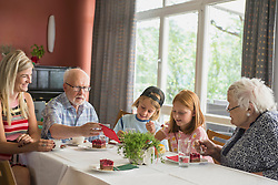 Family eating cake at rest home, Eichenau, Bavaria, Germany
