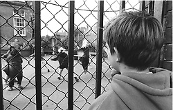 Young child looking through railings watching school children playing in playground,