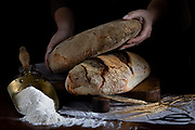Bread loaf in baker hands on rustic table with flour and wheat ears, dark moody setting.