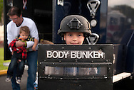 """19 MAY 2015 -- FENTON, Mo. -- Lance Roethlisberger, 7, tries on gear used by the St. Louis Metropolitan Police Department's SWAT team while posing for photographs for his mother Courtney Roethlisberger (not pictured) before a special Tuesday night church service """"Blessed are the Peacemakers: A Night of Honor"""" at LIFECHURCH in Fenton, Mo., Tuesday, May 19, 2015. The second annual service honored law enforcement officers, their families and supporters. Jon Belmar, St. Louis County Chief of Police, served as keynote speaker. Photo © copyright 2015 Sid Hastings."""