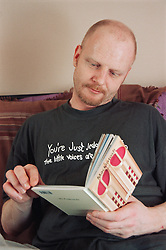 Portrait of male resident reading book in bedroom of homeless hostel for people with learning difficulties,