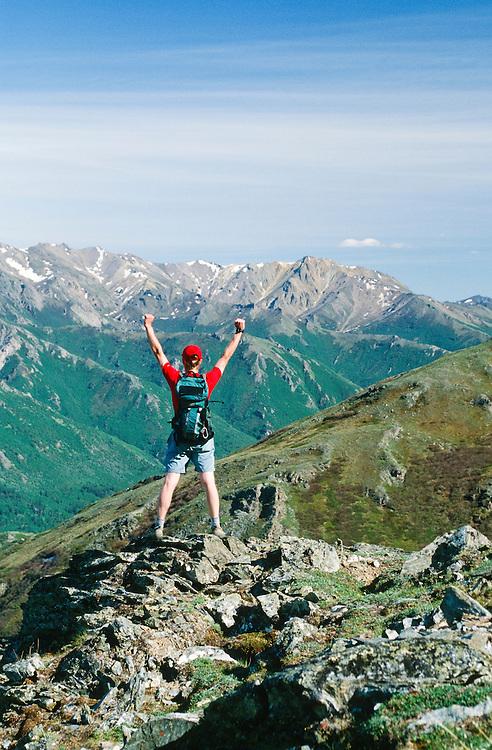 Alaska. Denali NP. HIker reaches a ridge and enjoys the summer view.