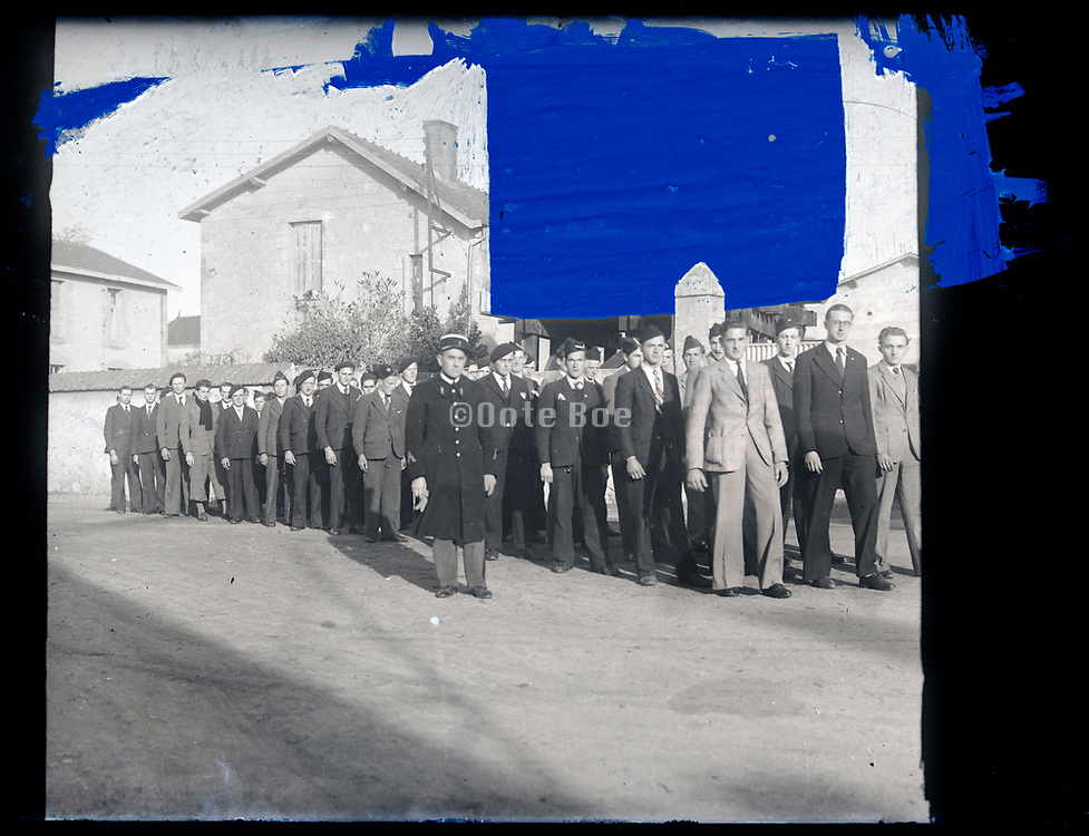 men in civil clothing marching with person in military uniform glass plate negative with retouch markings France circa 1930s