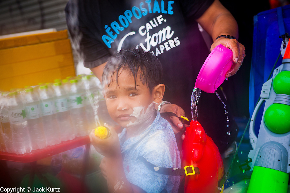 """13 APRIL 2013 - BANGKOK, THAILAND:  A Thai boy participates in a water fight on Khao San Road, which is Bangkok's """"backpacker"""" district, during Songkran celebrations in the Thai capital. Songkran is celebrated in Thailand as the traditional New Year's Day from 13 to 16 April. The date of the festival was originally set by astrological calculation, but it is now fixed. If the days fall on a weekend, the missed days are taken on the weekdays immediately following. Songkran is in the hottest time of the year in Thailand, at the end of the dry season and provides an excuse for people to cool off in friendly water fights that take place throughout the country. Songkran has been a national holiday since 1940, when Thailand moved the first day of the year to January 1.   PHOTO BY JACK KURTZ"""
