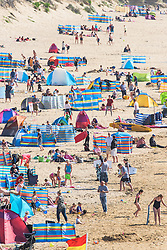 Holidaymakers enjoy the sunny weather on Fistral Beach in Newquay, Cornwall.