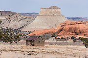A white mesa and log cabin south of Cannonville, Utah, USA.