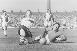 Tom Finney, Preston North End squeezes the ball past Harry Leyland, Blackburn Rovers goalkeeper.