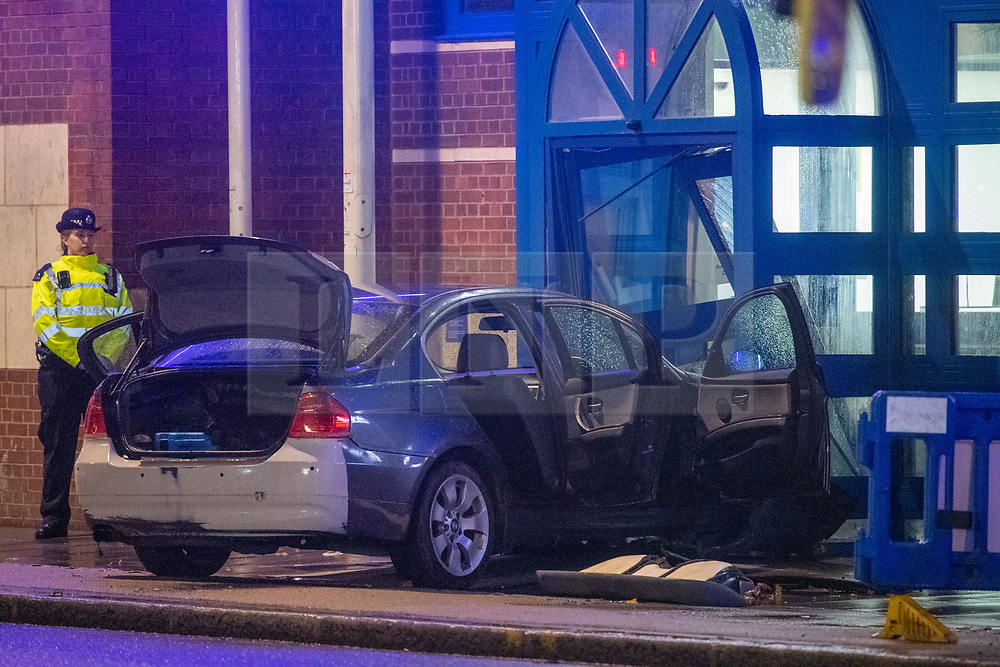 © Licensed to London News Pictures. 11/11/2020. London, UK. A police officer stands next to a damaged vehicle at the entrance of Edmonton police station. A vehicle has crashed into Edmonton police station, the incident occurred at approximately 18:58GMT. Photo credit: Peter Manning/LNP