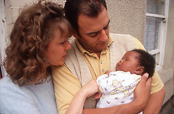 Mother and father standing outside holding young baby,