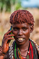 Young Hamer tribe woman talking on a mobile phone, Omo Valley, Ethiopia.