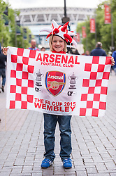 © Licensed to London News Pictures. 30/05/2015. London, UK. A young Arsenal supporter holds up a flag, as fans gather at Wembley Stadium for the FA Cup Final 2015, between Arsenal and Aston Villa. Photo credit : Stephen Chung/LNP