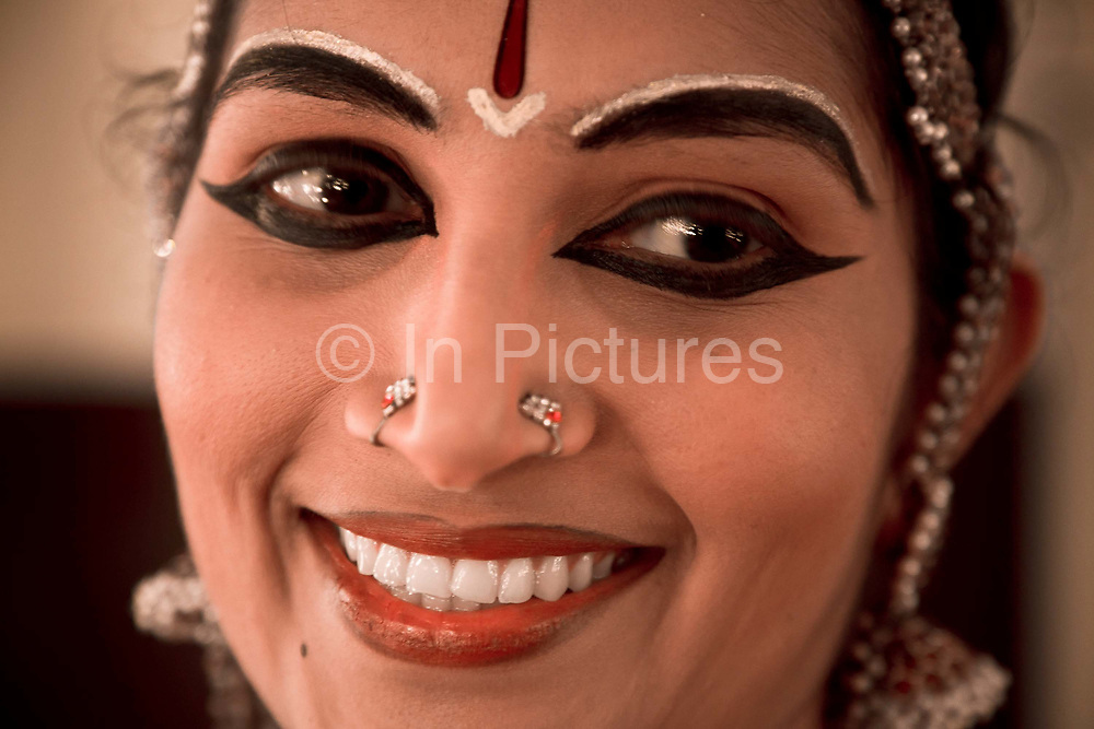 """Ganga Thampi, applies make up to her face shortly before taking the staring role of Sita in the Indian epic Ramayana. She is both a teacher and one of the stars of  the traditional and highly prestigious Kalakshetra school for the arts, Chennai. The school was founded in 1936 and due to its exacting and demanding schedule is considered India's formost classical dance academy of this ancient cultural art heritage that is informally known as """"temple dancing"""" and that dates back to the Natya Shastra, the 2000 year old text that lays down the principles of Indian dramatic theory and performance. Tamil Nadu, India."""
