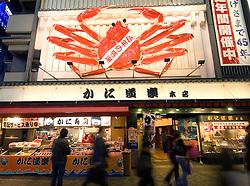 Large crab outside seafood restaurant at night in Dotonburi nightlife district of Osaka Japan