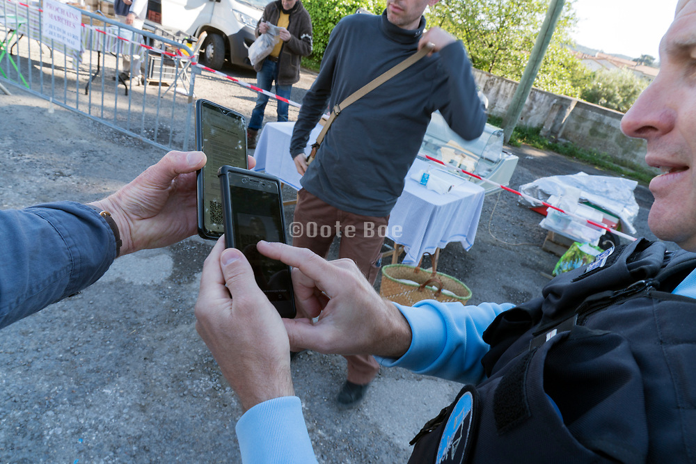 police scanning the French digital form  D'attestion de déplacement dérogatoire for being outside during Covid 19 crisis and lockdown France Limoux April 2020