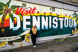 Glasgow, Scotland, UK. 7 October 2020. Time Out magazine has named Dennistoun in the East End of Glasgow as one of the world's coolest districts. Pictured; SNP MP for Glasgow North East constituency Anne McLaughlin poses in front of mural in Dennistoun following the district's new recognition. Iain Masterton/Alamy Live News