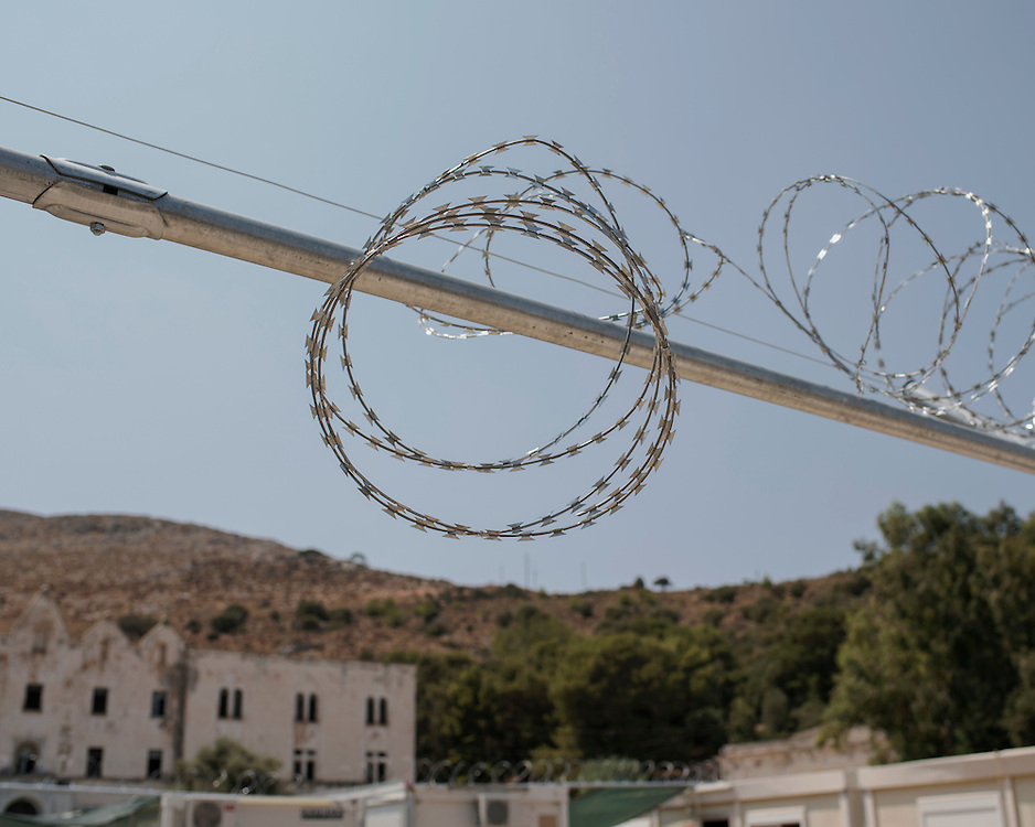 A barbed wired gate that separates the different communities of migrants and refugees into sections at the First Reception Centre (Hot-Spot) of Leros, Greece. <br /> <br /> The Hot Spot in Lepida opened on the 26th of February 2016 in the grounds of the former Lepida psychiatric hospital.  At the beginning it served as a registration camp for refugees and migrants who were travelling to Europe through Greece but since the closure of the borders in March 2016 it serves as a permanent camp. People are allowed to go out, they have three meals a day, the prefabricated huts have a bathroom and are air-conditioned and compering to other refugee camps in Greece the conditions are bearable.
