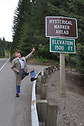 Humorous photograph of a man pointing to a HISTORICAL MARKER AHEAD sign that has been changed to read HYSTERICAL MARKER AHEAD.