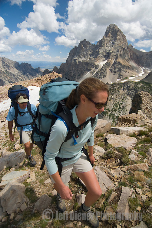 The Grand Teton looms behind a pair of hikers in the high alpine of the Teton Range, Wyoming.