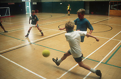 Group of young children playing game of football in sports hall,