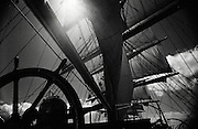 A black and white shot of a clipper ships sails, taken from the boat's main wheel