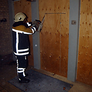 Brand oude gebouw Groene Kruis de Ruyterstraat Huizen, opening houten deur met kettingzaag door brandweer