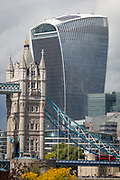 A London bus crosses the Thames river on the Victorian-era Tower Bridge, and in the background is the modern Walkie Talkie building aka 20 Fenchurch Street, on 14th September 2017, in London, England.