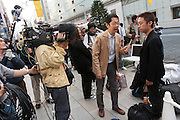 Takachiyo Yamanaka is interviewed by Japanese television as he stands in the lines of people at the Apple store awaiting the official release of the iphone4S in Ginza, Tokyo, Japan. Friday October 14th 2011. The latest version of the popular iphone was released worldwide on October 14th. Japans flagship Apple store in Ginza was opened at 8am for the 800 people that had been waiting to be the first to purchase the new telephone.