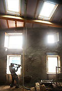 Builder wearing a safety mask spraying concrete on the walls of an ancient house in Lagrasse, France