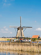Tourists on a boat enjoy a view of one the Kinderdijk Windmills, The Netherlands.