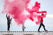 """Tamworth, United Kingdom, July 12, 2021: Activists from the """"Palestine Action"""" activist group light a red flare after they scaled the roof, daubed blood-red paint and smashed the windows across the Elite KL site on Amington Industrial Estate in Tamworth early on Monday, July 12, 2021. (VX Photo/ Vudi Xhymshiti)"""