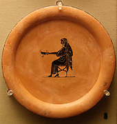 Black-figured plate: Dionysus, god of wine, seated holding out a drinking-cup. Made in Athens about 320-500BC attributed to the painter Psiax