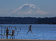 Kids perform off the diving board at Madrona Park on Lake Washington with a large mountain as their audience. (Steve Ringman / The Seattle Times)