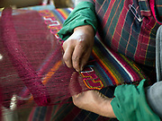 Weaving a woollen yathra blanket on a Tibetan style loom in Chumey village, Bumthang, Central Bhutan. Yathra is a hand woven fabric made from the wool of sheep and yak and is the most famous textile product of Bumthang. Yathra cloth is made into skarfs, jackets, blankets, tablecloths and bags.