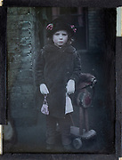 Colourised magic lantern slide portrait of a young girl dressed up in adult clothing, circa 1900