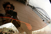 Self-portrait of photographer Luis Filipe Catarino reflected in the Opera House building in Sydney harbour.