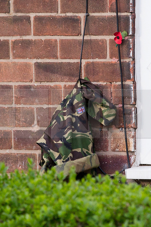 © Licensed to London News Pictures . 13/11/2012 . Manchester , UK . A single poppy and army fatigues hang on the wall outside the front door of the family home of British soldier , Drummer Lee Rigby of the 2nd Battalion Royal Regiment of Fusiliers , in Middleton . Drummer Rigby was murdered in Woolwich yesterday (Wednesday 23rd May) . Photo credit : Joel Goodman/LNP